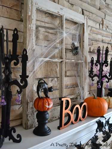 A $4 weathered window frame takes center stage on this mantel, while candelabras, pumpkins, and pops of purple add to the tableau.