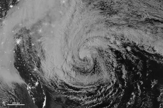 """Hurricane Sandy was captured at 2:42 a.m. Eastern Daylight Time on October 28, 2012 by a special """"day-night band,"""" on Suomi NPP satellite, which detects light in a range of wavelengths from green to near-infrared and uses filtering techniques to observe dim signals such as auroras, airglow, gas flares, city lights, fires, and reflected moonlight. In this case, cloud tops were lit by the nearly full moon. Some city lights in Florida and Georgia are also visible through the clouds."""