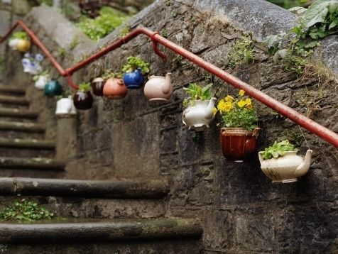 teapot planters hung on stair railing - cute decor for a rustic/vintage wedding