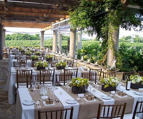 For an outdoor event, top white linens with burlap runners and simple, understated dishes and glassware.