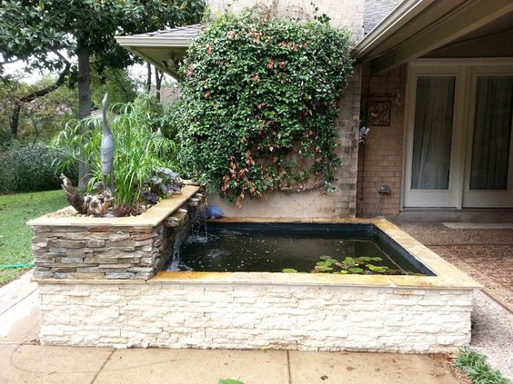 Side view of an modern above ground koi pond with stacked for Above ground fish pond designs