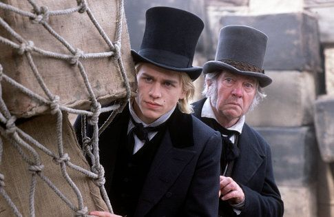 Nicholas Nickleby (CHARLIE HUNNAM) and Newman Noggs (TOM COURTENAY) keep an eye on mischief