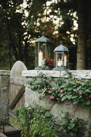 Candle lanterns on stone wall   photography by http://photography.michelemwaite.com/