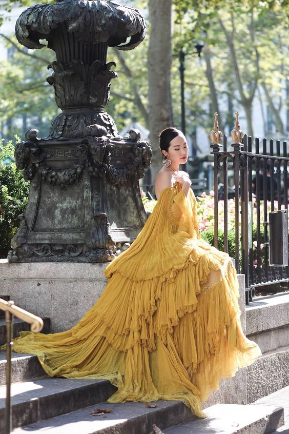 A Modern Fairy Tale - #ChriselleLim shines bright in this yellow off-the-shoulder ruffle plisse gown from the #RobertoCavalliFW16 collection featured in #ElleHongKong.  Discover more dresses: http://bit.ly/2gXV10E