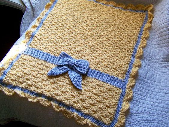 Crochet baby blanket with a bow.