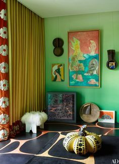 Artworks—including a large Ken Kiff piece and a Yayoi Kusama gourd—occupy a corner of a living area | archdigest.com
