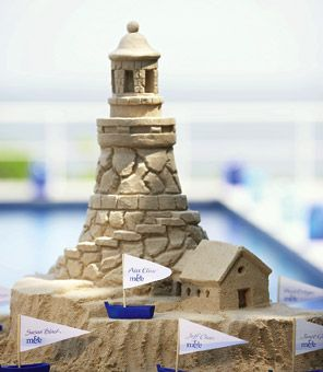 Beautiful Sand Castle Lighthouse with adorable Boat Favor Boxes is a wonderful Centerpiece at the Wedding. Favor boats found at www.bellaparisboutique.com: