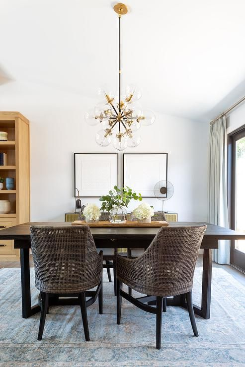 Brown Wicker Chairs At A Dark Brown Wooden Dining Table Illuminated By An Atom Chandelier In A Trans Brown Dining Room Dark Dining Room Dark Brown Dining Table
