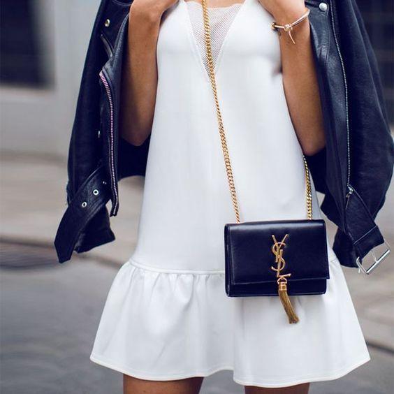 Look vestido curto branco, jaqueta de couro e bolsa com alça de corrente.