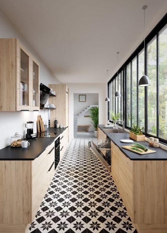 Cuisine bois avec plan de travail noir, carrelage carreaux de ciment et fenêtres verrière d'atelier