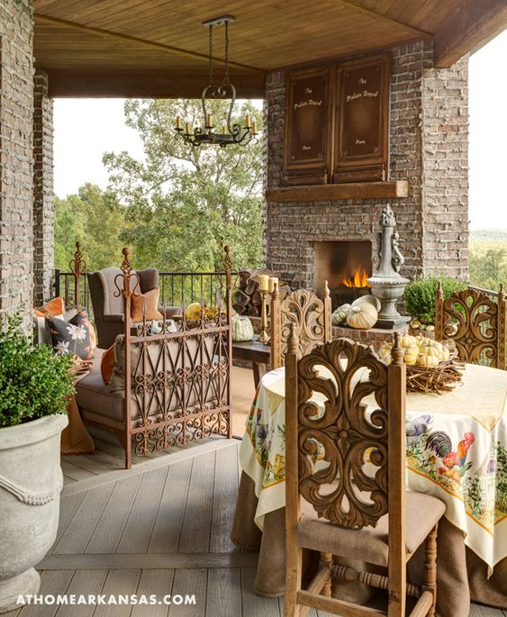 The porch wraps around the home and provides multiple activity zones for enjoying the view in fine weather. Just as in the home's interior, a mix of custom, antique, and reproduction pieces create an Old World-atmosphere that is luxurious and inviting. At Home in Arkansas | November 2015