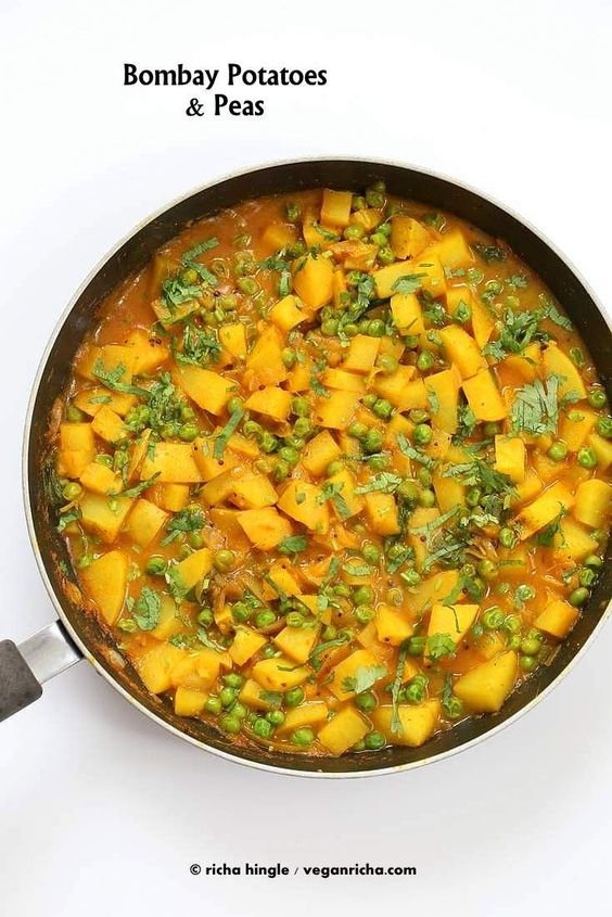 These Bombay potatoes are super easy and delicious. Potatoes and peas cooked in an easy onion tomato and spice sauce and garnished liberally with cilantro.