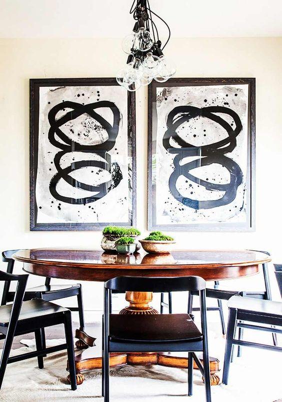 idée déco salle à manger - ensemble de deux tableaux en noir et blanc à proximité de la table ronde en bois massif entourée de chaises noires