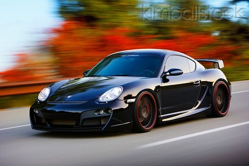 POR 04 RK0795 01 - 2008 Porsche Cayman S TechArt Black 3/4 Front View Driving By Foliage - Kimballstock
