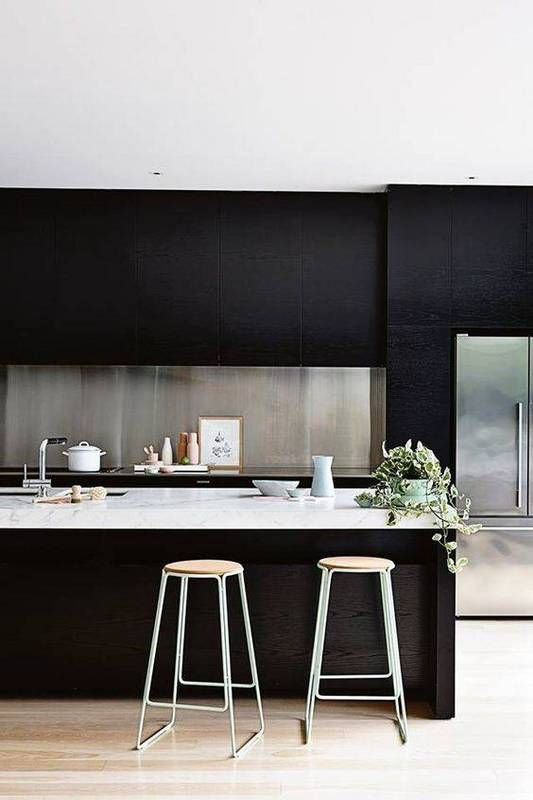 Kitchen with bold black cabinets and stainless steel backsplash