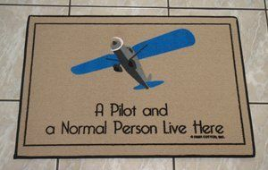 "Pilot and Normal Person Live Here Door Mat by High Cotton. $21.59. Unique aviation humor. Indoor or outdoor. Non-skid backing. Waterproof. Whether inside or out, add a bit of humor to your home with a Doormat that is sure to make visitors smile. Waterproof, UV stable carpet features pilot wings and a durable non-skid backing making it at home inside or out. Measures 18"" x 30""."