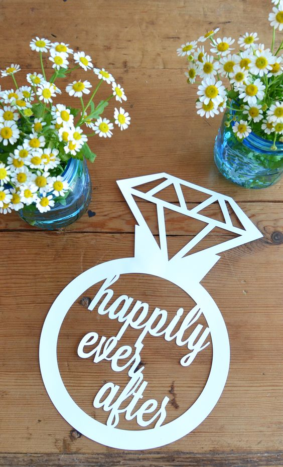 """This delicate paper cut sign is the perfect gift for a newly engaged bride or decor for a bridal shower or engagement party. The design is cut from a single piece of card stock and is approximately 8"""""""