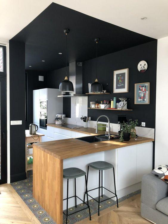 Jouez avec la peinture des meubles et du plafond pour délimiter des pièces sans cloisonner. Ici très réussie pour une cuisine aux meubles blancs mais aux murs noirs.