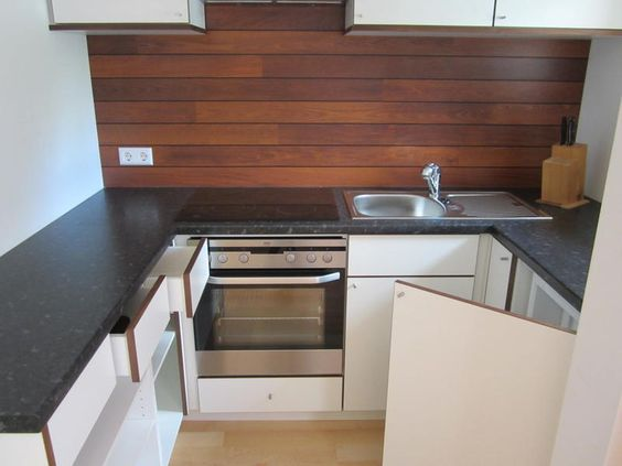 Küchenrückwand aus Holz, die geschickt den Ton der Türkanten aufgreift.