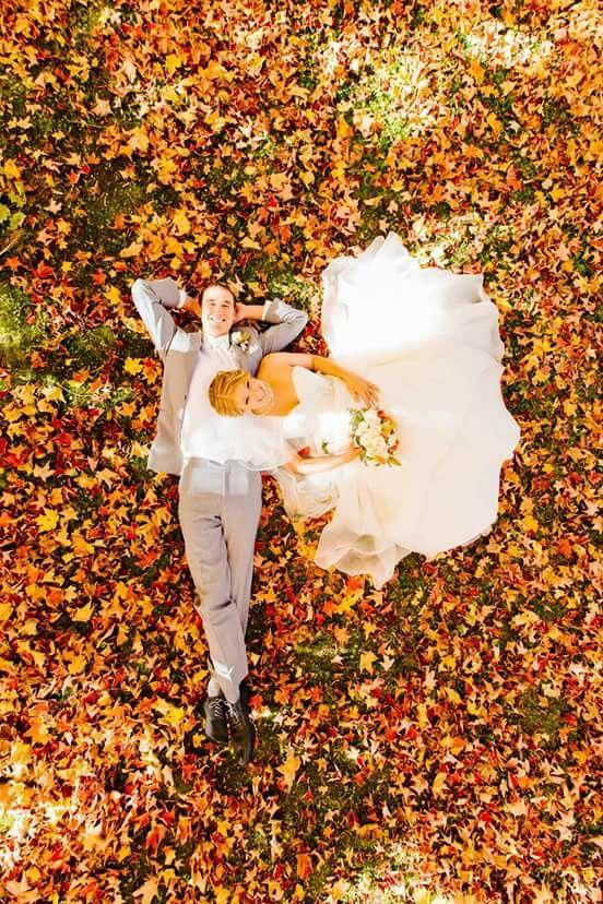 Foto de vista superior - casal deitado na grama/folhagens outono