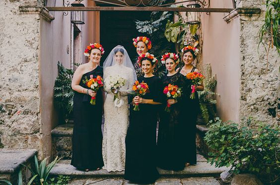 Bridesmaids in black dresses with bright flower crowns