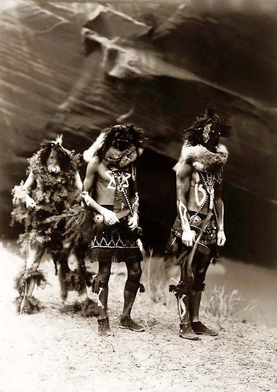 Here for your consideration is an old picture of Yebichai, Indian War Gods. It was created in 1904 by Edward S. Curtis.    The photograph presents Three Indians: Tonenili, Tobadzischini, and Nayenezgani, in ceremonial dress, photographed against dark rock background.    We have created this collection of illustrations primarily to serve as a valuable educational tool. Contact curator@old-picture.com.    Image ID# ADCAF023: