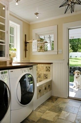 what a great idea. In this gorgeous laundry room their is a tub for watering plants that has a handheld hose for showering the dogs and when not in use a counter on top to use it to fold laundry! Genius