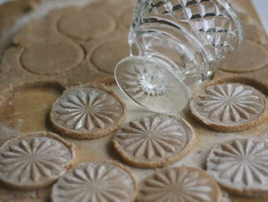 After cutting out rounds of cookie dough, create a pattern by using the bottom of a fancy glass.  Simply dip the glass in some flour, then press the glass into the cookie dough to create an imprint.  Use a pastry brush to remove the excess flour from the cookie.
