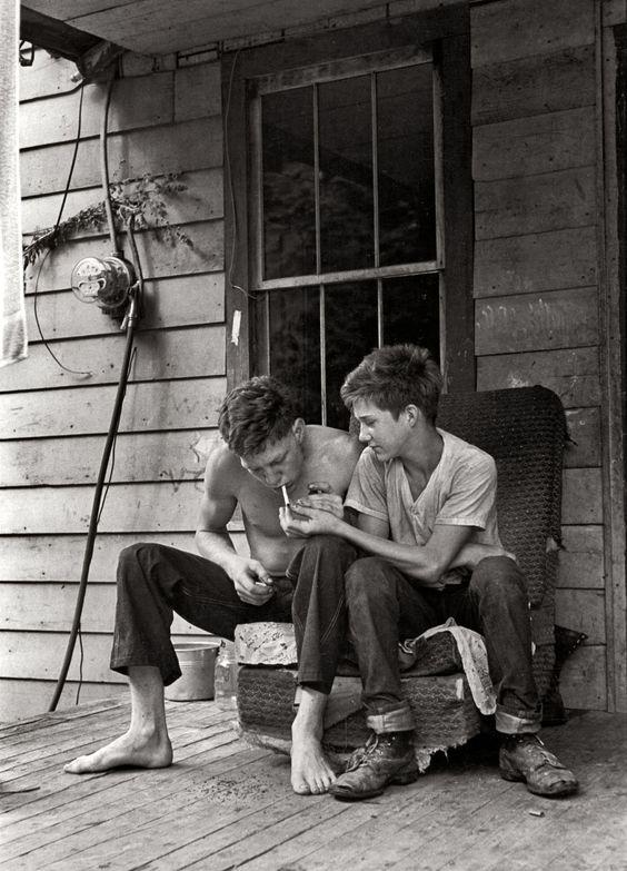 Boys sitting on porch lighting cigarette.Leatherwood, Kentucky, 1964. By William Gedney