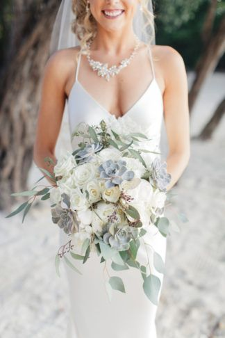 I wanted a very natural-looking bouquet – all white florals with lots of greenery throughout for our Key Largo wedding. I included seeded eucalyptus and succulents., along with white hydrangeas and roses.