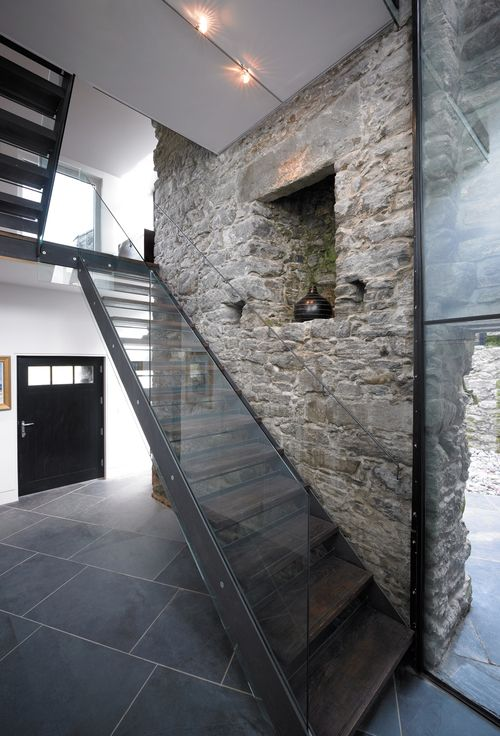 Treppe aus Stahl und Glas in renoviertem Steinhaus