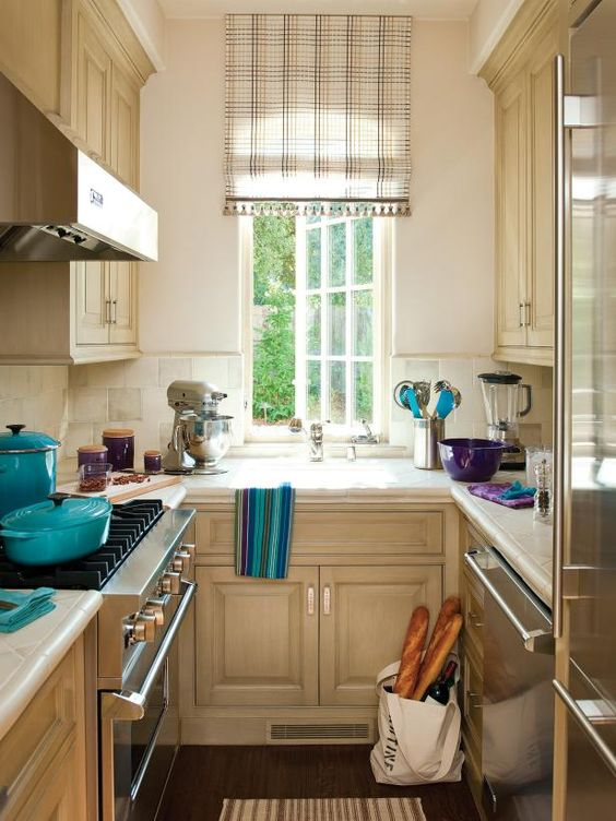 Betty Lou Phillips creates a galley kitchen with style! HGTV shares a galley kitchen with neutral walls and cabinets that incorporates pops of color in the accessories.