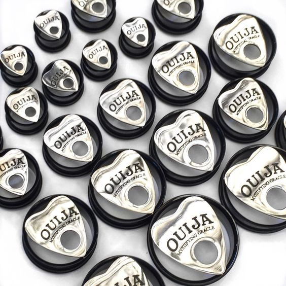 "This is a pair of ear plugs featuring a ouija pendant on the front of black tunnels. The tunnels have an 'o' ring  at the back to secure the plug in your ear.These plugs are available in the following sizes:10mm (00g)12mm (1/2"")14mm 16mm (5/8"")18mm (11/16"")20mm (3/4"")22mm 24mm (1"")26mm 28mm30mm*Please note we do not take responsibility for blow outs. Please take into consideration the size and weight when purchasing ear stre..."