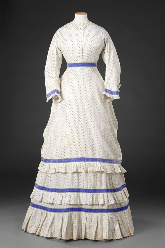 Dress Circa 1869-70 Cotton, trimmed with cotton braid Acquired from the collection of the costume designer Shirley Russell. This one-piece dress of white cotton printed with a small black abstract motif, and trimmed with bright blue cotton braid, has a matching separate apron overskirt, a popular new feature of late 1860s and early 1870s fashion.