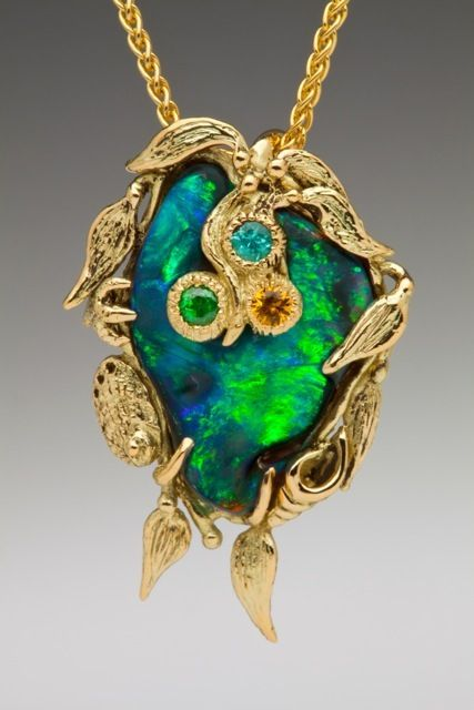 This one of a kind pendant is cast in 18K gold. Undulating seaweed frames a 6 carat Australian Boulder Opal, shimmering with the intoxicating colors of a tropical reef. A tsavorite, yellow sapphire and pariba tourmaline are set within the three sea anemones. Also tucked amidst the seaweed is a tiny abalone, star fish and sea shell. The pendant is 1 3/8""