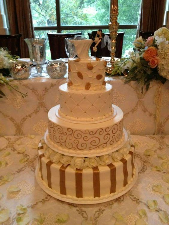 This large 4-tier wedding cake was accented with lots of hand painted gold details on every tier. #wedding #weddingcakes #elegant