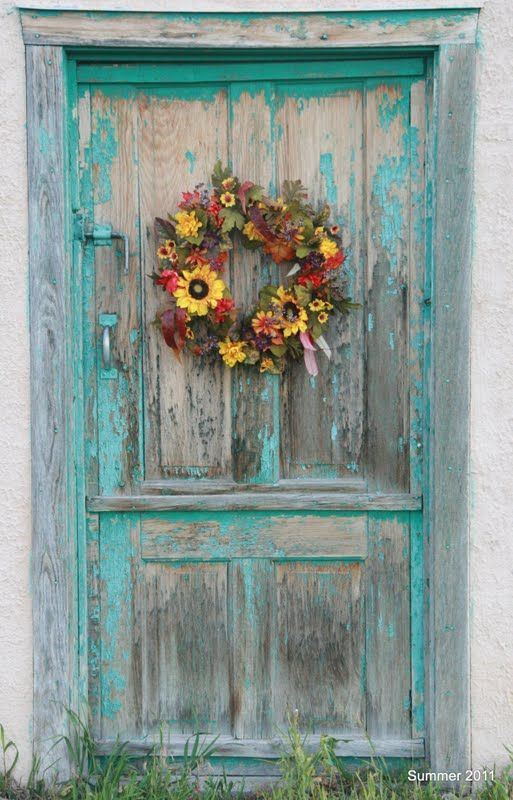 Blue Chipped Paint and Bright Yellow Wreath make this door an eye-pleasing art piece.  Do your thing today with wreaths from CCL Ranch Decor.com