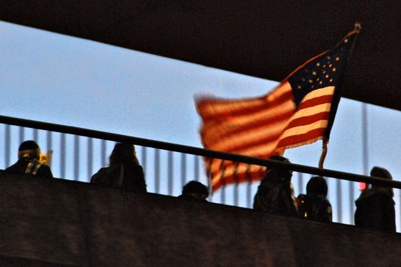 Occupy Seattle protestors crossed the lower level Spokane Street bridge to close Terminal 5, waving an American flag