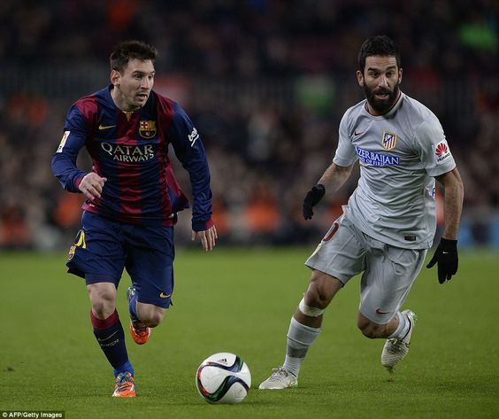 Atletico's Arda Turan (right) and Barca's Messi run to try and compete for the ball during...
