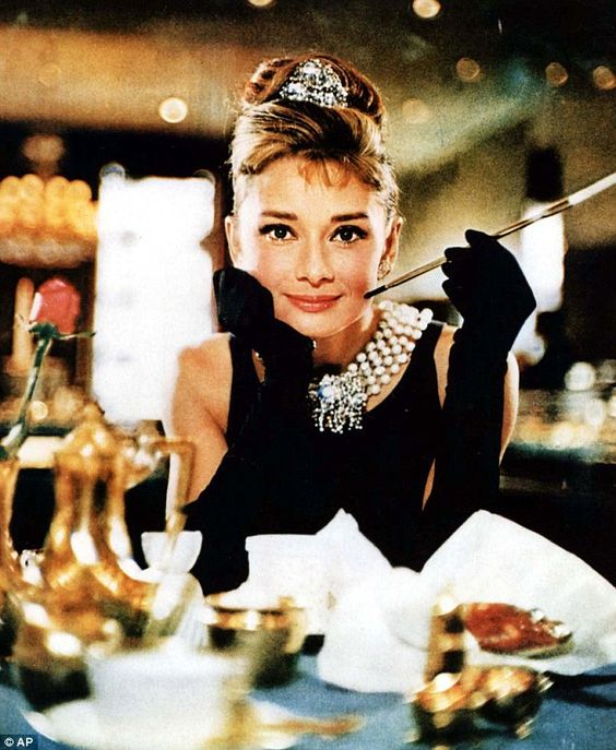 Audrey Hepburn strikes the Breakfast at Tiffany's pose in a black cocktail dress, gloves a...
