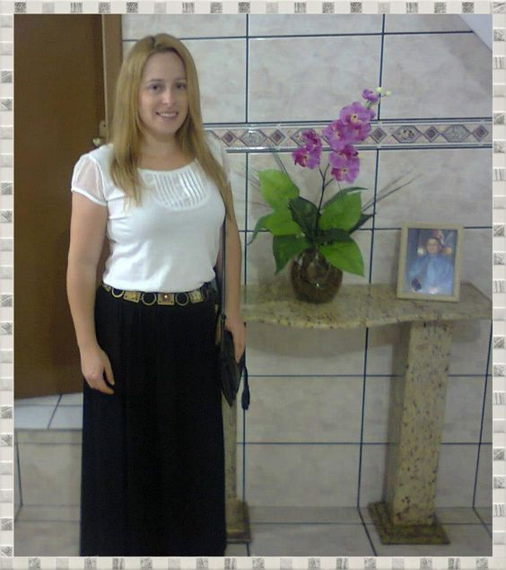 Blusinha Branca, saia preta longa, sinto de flor em couro e bolsa preta.