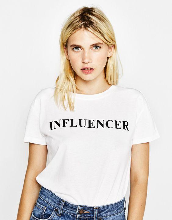 Camiseta blanca con letras negras.