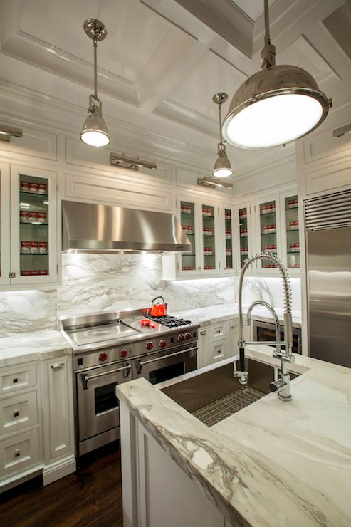 Gorgeous kitchen with picture lights illuminating glass-front upper cabinets and inset lower ...