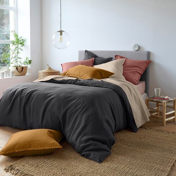 Draps et coussins en lin dans une chambre à l'ambiance naturelle