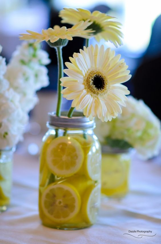 Mason jars filled with lemon slices and gerber daisies