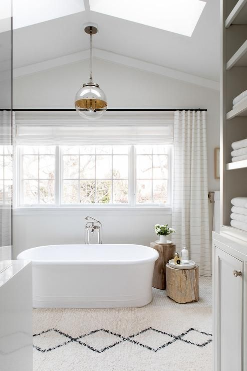 Hung From A Vaulted Ceiling Fitted With Skylights A Glass Globe Pendant Lights An Oval Frees Beautiful Small Bathrooms Bathroom Lighting Design Small Bathroom