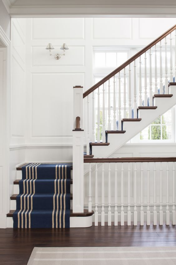 White, navy and wood staircase with a striped runner and paneling. Not a huge fan of these sconces at first, but they are growing on me.: