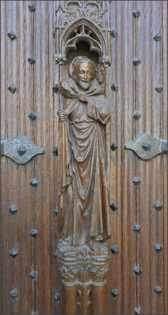 Detail of a wooden door of the Saint Bavo cathedral in Ghent, next to the main entrance of the cathedral, Belgium. Wood carving of Saint Bavo.: