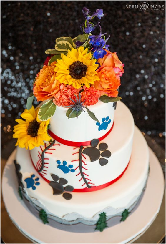 A baseball and pet themed wedding cake from Azucar with flowers on a black sequin backdrop at the Hyatt Regency DTC in Colorado. - April O'Hare Photography http://www.apriloharephotography.com