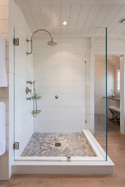 Amazing shower features walls clad in corian sheets to mimic shiplap lined with a Waterworks Henry Gooseneck Wall Mounted Shower Head over a gray hex tiled floor in Bardiglio Marble.